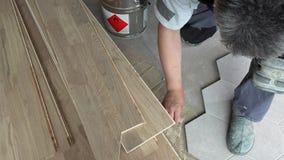 Το άτομο με spatula εφαρμόζει την κόλλα κόλλας στο πάτωμα κοντά στα hexagon κεραμίδια απόθεμα βίντεο