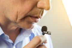 Το άτομο μιλά σε ένα μικρό μικρόφωνο σε μια χαμηλή φωνή Στοκ Εικόνες