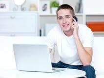 Το άτομο μιλά στο τηλέφωνο και εργάζεται στο lap-top Στοκ φωτογραφίες με δικαίωμα ελεύθερης χρήσης