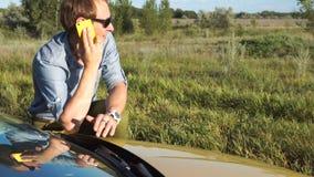 Το άτομο μιλά στο τηλέφωνο κοντά στο αυτοκίνητο απόθεμα βίντεο
