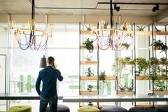 Το άτομο μιλά στο τηλέφωνο από την πίσω πλευρά στο πράσινο δωμάτιο του γραφείου Στοκ εικόνες με δικαίωμα ελεύθερης χρήσης