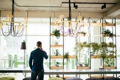 Το άτομο μιλά στο τηλέφωνο από την πίσω πλευρά στο πράσινο δωμάτιο του γραφείου Στοκ φωτογραφίες με δικαίωμα ελεύθερης χρήσης