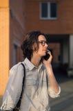 Το άτομο μιλά στο smartphone μπροστά από το σύγχρονο κτήριο Στοκ Εικόνα