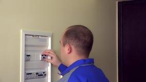 Το άτομο μπλε σε ομοιόμορφο ανοίγει τους διακόπτες στο κιβώτιο επιτροπής στο επίπεδο σπίτι απόθεμα βίντεο