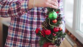 Το άτομο ντύνει όμορφος λίγο καμμένος χριστουγεννιάτικο δέντρο φιλμ μικρού μήκους