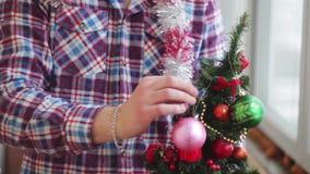 Το άτομο ντύνει όμορφος λίγο καμμένος χριστουγεννιάτικο δέντρο απόθεμα βίντεο