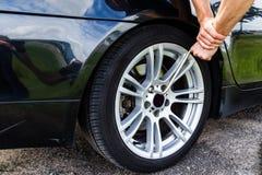 Το άτομο ξεβιδώνει τα μπουλόνια της οπίσθιας ρόδας το αυτοκίνητο για να αλλάξει τις ρόδες Στοκ εικόνα με δικαίωμα ελεύθερης χρήσης