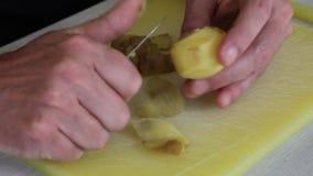 Το άτομο ξεφλουδίζει τις πατάτες απόθεμα βίντεο