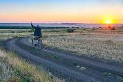 Το άτομο οδηγά ένα ποδήλατο στη χώρα στον τομέα το βράδυ Στοκ φωτογραφία με δικαίωμα ελεύθερης χρήσης
