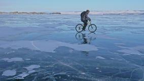 Το άτομο οδηγά ένα ποδήλατο στον πάγο Ο ποδηλάτης είναι ντυμένος σε ένα γκρίζα κάτω σακάκι, ένα σακίδιο πλάτης και ένα κράνος Πάγ φιλμ μικρού μήκους