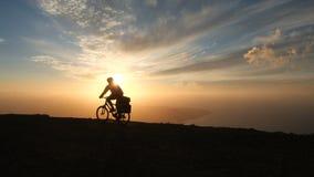 Το άτομο οδηγά ένα ποδήλατο υψηλό στα βουνά κοντά στην άκρη απότομων βράχων επάνω από τον ωκεανό στο όμορφο δραματικό κλίμα ηλιοβ φιλμ μικρού μήκους