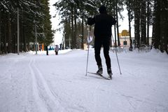 Το άτομο οδηγά ανώμαλο να κάνει σκι Να ανεβεί την κλίση με άλλη ακολουθία σκιέρ Στοκ Φωτογραφία