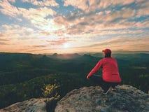 Το άτομο οδοιπόρων παίρνει ένα υπόλοιπο στην αιχμή βουνών Το άτομο βάζει στη σύνοδο κορυφής, στοκ εικόνες