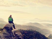 Το άτομο οδοιπόρων παίρνει ένα υπόλοιπο στην αιχμή βουνών Το άτομο κάθεται στην αιχμηρή σύνοδο κορυφής και απολαμβάνει τη θεαματι Στοκ Εικόνες