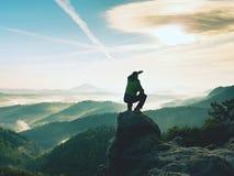Το άτομο οδοιπόρων παίρνει ένα υπόλοιπο στην αιχμή βουνών Το άτομο κάθεται στην αιχμηρή σύνοδο κορυφής και απολαμβάνει τη θεαματι Στοκ φωτογραφίες με δικαίωμα ελεύθερης χρήσης