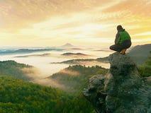 Το άτομο οδοιπόρων παίρνει ένα υπόλοιπο στην αιχμή βουνών Το άτομο κάθεται στην αιχμηρή σύνοδο κορυφής και απολαμβάνει τη θεαματι Στοκ φωτογραφία με δικαίωμα ελεύθερης χρήσης