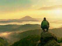 Το άτομο οδοιπόρων παίρνει ένα υπόλοιπο στην αιχμή βουνών Το άτομο κάθεται στην αιχμηρή σύνοδο κορυφής και απολαμβάνει τη θεαματι Στοκ εικόνες με δικαίωμα ελεύθερης χρήσης