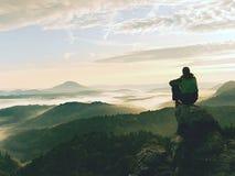 Το άτομο οδοιπόρων παίρνει ένα υπόλοιπο στην αιχμή βουνών Το άτομο κάθεται στην αιχμηρή σύνοδο κορυφής και απολαμβάνει τη θεαματι Στοκ εικόνα με δικαίωμα ελεύθερης χρήσης