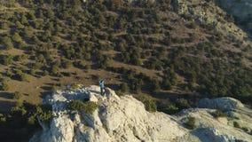 Το άτομο ορειβατών στέκεται πάνω από το βράχο και αυξάνει τα χέρια νικηφόρα εναέρια όψη φιλμ μικρού μήκους