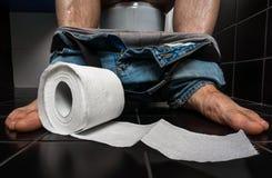 Το άτομο πάσχει από τη διάρροια κάθεται στο κύπελλο τουαλετών στοκ εικόνες με δικαίωμα ελεύθερης χρήσης