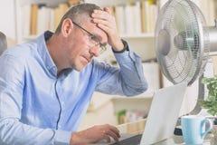 Το άτομο πάσχει από τη θερμότητα στο γραφείο ή στο σπίτι στοκ εικόνα