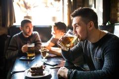 Το άτομο πίνει την μπύρα μπροστά από στη συζήτηση των πίνοντας φίλων στο μπαρ Φίλοι στο μπαρ Στοκ Φωτογραφία