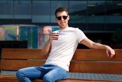 Το άτομο πίνει τον καφέ πρωινού για να πάει, καθμένος στον πάγκο Παίρνοντας το σπάσιμο από τη βιασύνη πόλεων, θέτοντας και απολαμ στοκ εικόνα