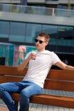 Το άτομο πίνει τον καφέ πρωινού για να πάει, καθμένος στον πάγκο Παίρνοντας το σπάσιμο από τη βιασύνη πόλεων, θέτοντας και απολαμ στοκ εικόνες με δικαίωμα ελεύθερης χρήσης