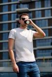 Το άτομο πίνει τον καφέ πρωινού για να πάει Παίρνοντας ένα σπάσιμο από τη βιασύνη πόλεων, θέτοντας και απολαμβάνοντας μια όμορφη  στοκ φωτογραφία με δικαίωμα ελεύθερης χρήσης