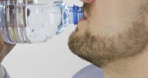 Το άτομο πίνει το νερό από ένα πλαστικό μπουκάλι κλείστε επάνω απόθεμα βίντεο