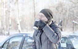 Το άτομο πίνει το τσάι από την κούπα υπαίθρια στο χειμερινό δρόμο Στοκ φωτογραφίες με δικαίωμα ελεύθερης χρήσης