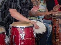 Το άτομο παίζει τα μεξικάνικα τύμπανα conga παίζοντας μεταξύ άλλων εμπρός στοκ εικόνες