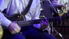 Το άτομο παίζει την ηλεκτρική κιθάρα στην ορχήστρα τζαζ φιλμ μικρού μήκους