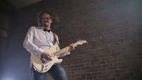 Το άτομο παίζει την κιθάρα Ορχήστρα ροκ συναυλίας που αποδίδει στη σκηνή Σε αργή κίνηση παιχνίδι οργάνων φιλμ μικρού μήκους