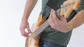 Το άτομο παίζει τη βαθιά κιθάρα και το άλμα στη μουσική - πορτρέτο του πυροβολισμού συνδετήρων που απομονώνεται στο λευκό φιλμ μικρού μήκους
