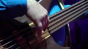Το άτομο παίζει τη βαθιά κιθάρα απόθεμα βίντεο