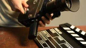 Το άτομο παίρνει έναν μηχανισμό άνοιξη σε μια αναδρομική κάμερα κινηματογράφων απόθεμα βίντεο