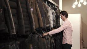 Το άτομο παίρνει το μαύρο σακάκι από την κρεμάστρα σε ένα κατάστημα και φορά σε τον απόθεμα βίντεο