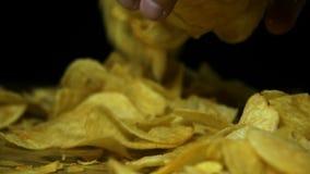 Το άτομο παίρνει τα τσιπ πατατών με το χέρι σε έναν ξύλινο πίνακα στο μαύρο υπόβαθρο σε σε αργή κίνηση απόθεμα βίντεο