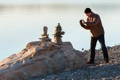 Το άτομο παίρνει την εικόνα των ισορροπώντας βράχων στοκ φωτογραφία