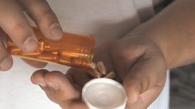 Το άτομο παίρνει τις βιταμίνες χαπιών ή οι ταμπλέτες φαρμάκων υπό εξέταση από το μπουκάλι χαπιών, κλείνουν επάνω Στοκ Εικόνα