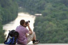Το άτομο παίρνει τις εικόνες από έναν λόφο στο υπόβαθρο του δάσους και του ποταμού Στοκ φωτογραφία με δικαίωμα ελεύθερης χρήσης