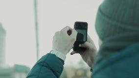 Το άτομο παίρνει τις εικόνες στηριγμένος στο smartphone απόθεμα βίντεο