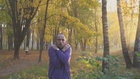 Το άτομο παγώνει στο πάρκο φθινοπώρου, που θερμαίνει τα χέρια ψυχρά φιλμ μικρού μήκους