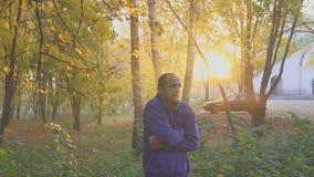 Το άτομο παγώνει στο πάρκο φθινοπώρου, που θερμαίνει τα χέρια ψυχρά απόθεμα βίντεο