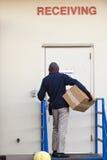 Το άτομο παράδοσης με το κιβώτιο παραδίδει το φορτίο στην πόρτα receiveng Στοκ Εικόνες