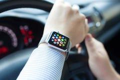 Το άτομο παραδίδει το αυτοκίνητο με το ρολόι και το εικονίδιο της Apple Στοκ Εικόνες