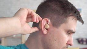 Το άτομο παρεμβάλλει μια ενίσχυση ακρόασης στο αυτί της απόθεμα βίντεο
