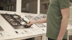 Το άτομο περιστρέφεται τις λαβές της μαγειρεύοντας επιτροπής εκθεμάτων σε ένα κατάστημα, κινηματογράφηση σε πρώτο πλάνο απόθεμα βίντεο