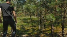 Το άτομο περνά από τα δέντρα στο ξύλο απόθεμα βίντεο